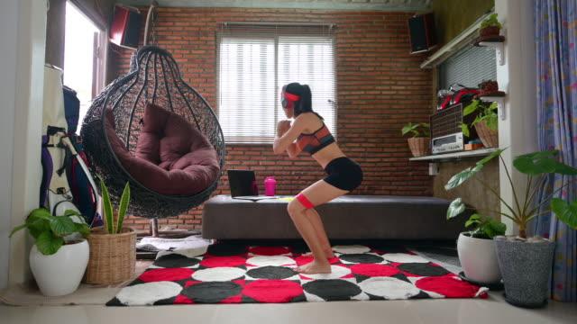 自宅でアジアの女性ワークアウト - ほっそりした点の映像素材/bロール