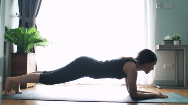 asian woman workout clothes is doing a plank exercise - plank stock videos & royalty-free footage