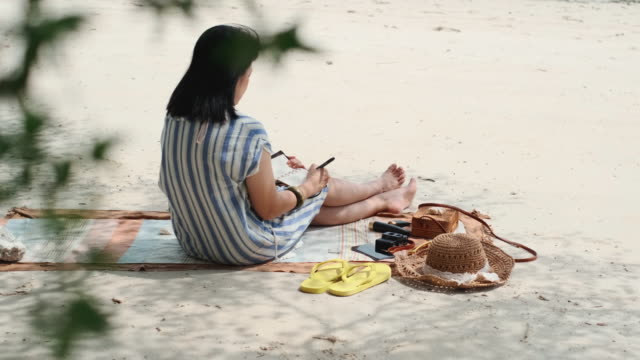 asian woman writing new year resolution for next year sitting at beach on summer vacation time - resting stock videos & royalty-free footage