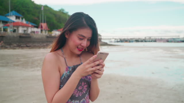 asian women, 30-40 years old, typing messages, talking to friends and smiling happily on the beach. - choosing stock videos & royalty-free footage