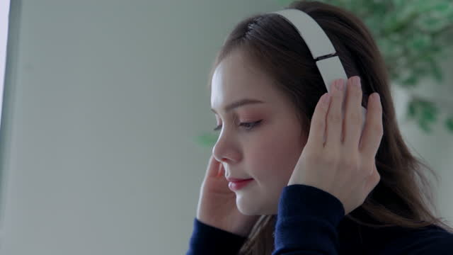 asiatische frauen im alter von 20-30 jahren, in lässiger kleidung gekleidet, tragen kopfhörer, um filme zu sehen oder musik online auf ihren computern zu hören. - weibliche angestellte stock-videos und b-roll-filmmaterial
