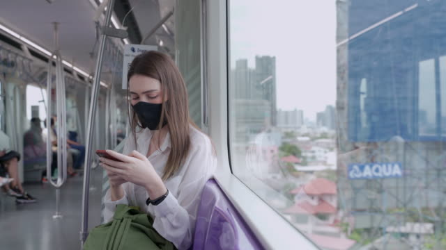 asian women aged 20-30 years old wearing surgical protective mask using a phone or smartphone while traveling on the bublic train transportation system in thailand - arrival stock videos & royalty-free footage