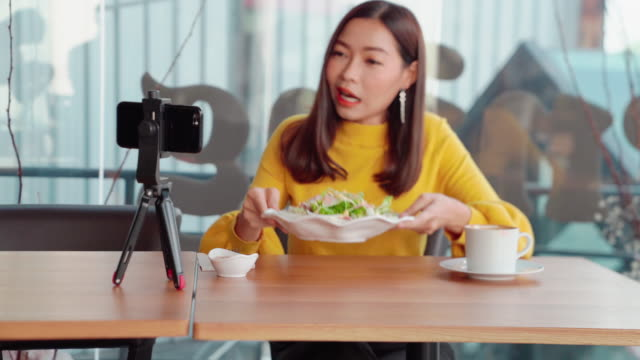 asian women aged 20-30 years, she was wearing a casual lifestyle and live my own vlog, tourism and restaurants, sitting on a table in a restaurant with live cameras. food and salad vegetables - social issues stock videos & royalty-free footage