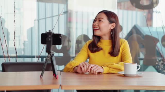 vídeos y material grabado en eventos de stock de mujeres asiáticas de 20-30 años, llevaba un estilo de vida informal y vivía mi propio vlog, turismo y restaurantes, sentado en una mesa en un restaurante con cámaras en vivo. verduras de comida y ensalada - entrevista grabación