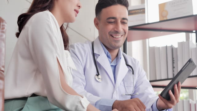 asian women and caucasian male doctor using tablet while in consultation to her female patient at hospital.male medical staff - emotional support stock videos & royalty-free footage