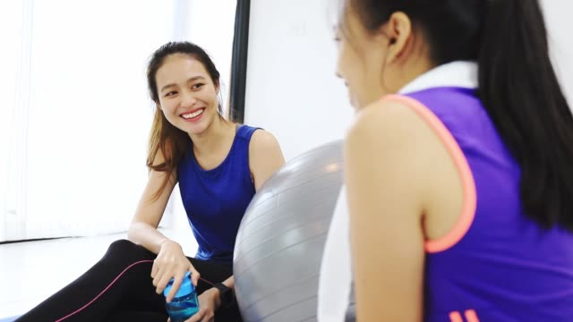 stockvideo's en b-roll-footage met aziatische vrouwen en vriend praten samen en rust na het spelen yoga en lichaamsbeweging thuis achtergrond met kopieerruimte. oefening voor afvallen, verhoging van de flexibiliteit en draai de vorm. - aerobics