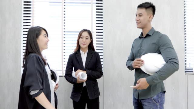 アジアの女性と男性技術者ビジネス プロジェクトについて議論して屋内で笑顔 - スポーツヘルメット点の映像素材/bロール