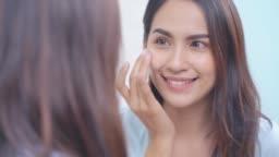 Asian women applying face lotion.