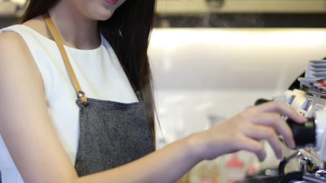 アジアの女性バリスタの笑顔しコーヒーのコーヒー マシンを使用してのショップ カウンター - 働く女性小企業所有者食べ物飲食カフェのコンセプト - 制服点の映像素材/bロール