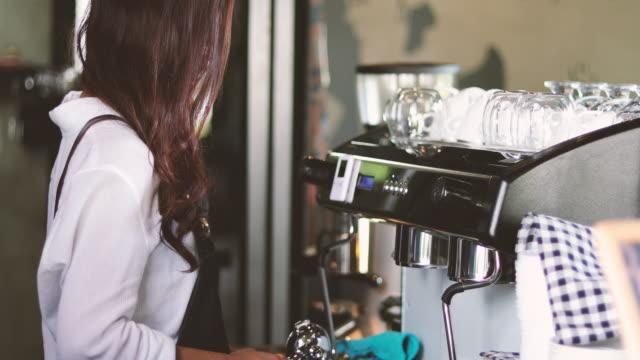 Asiatische Frauen Barista lächelnd und mit Kaffee aus dem Automaten im Kaffee shop counter - arbeitenden Frau Kleinunternehmen Besitzer Essen und trinken Café-Konzept