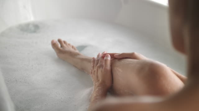 asian women bathing on her leg in the bathtub - vasca da bagno video stock e b–roll