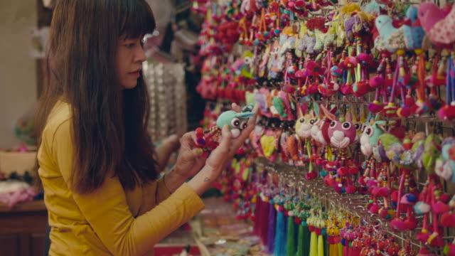 stockvideo's en b-roll-footage met aziatische vrouwen kopen geschenk op rommelmarkt. - rommelmarkt