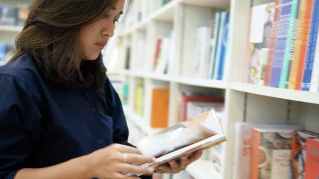 vídeos de stock e filmes b-roll de asian women choosing book in library - arquivista