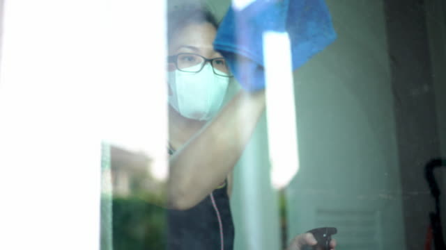 asian women cleaning glass doors for protect covid-19 - collaboratore domestico video stock e b–roll