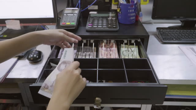 asian women dispensing change and counting from a register cash drawer - till stock videos & royalty-free footage