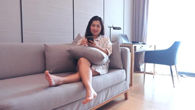 ソファでスマートフォンを楽しむアジアの女性 - くつろぐ点の映像素材/bロール