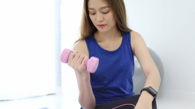 asian women exercise by lifting dumbbells at home background.exercise for lose weight, increase flexibility and tighten the shape. - tights stock videos & royalty-free footage