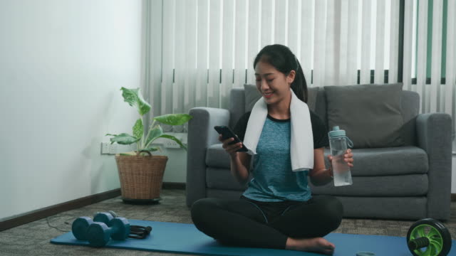 asian women exercise indoors while taking a break drinking water and playing mobile phones at home. - sportswear stock videos & royalty-free footage