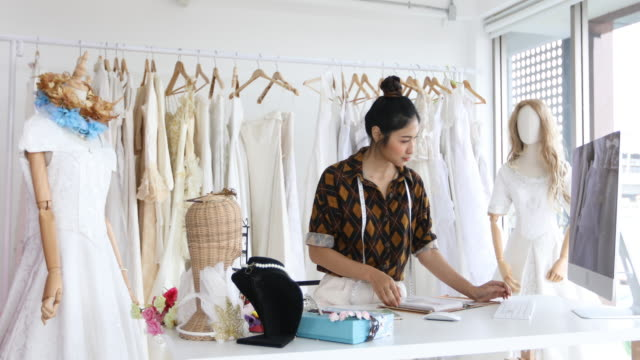 asian women fashion designer working and using smart phone and tablet with wedding dresses at at clothing store - fashion designer stock videos & royalty-free footage