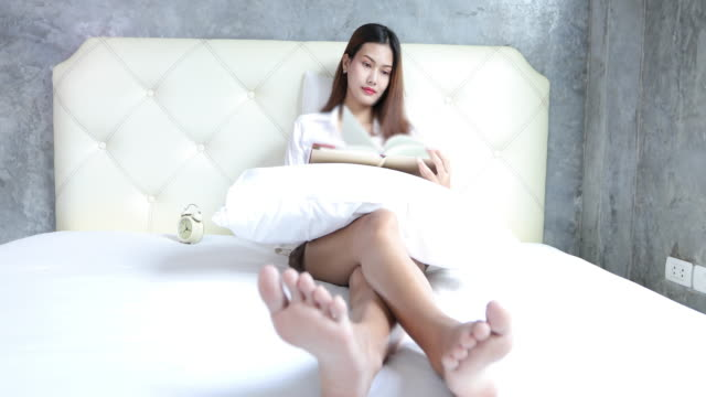 Asian women  favorite reading book at White bedroom shot on Amazing time to relax