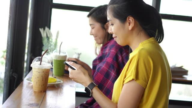 vídeos de stock, filmes e b-roll de apreciação de amigos de mulheres asiáticas falando no telefone inteligente e beber café sentado no café. - smart