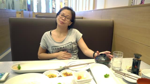 vidéos et rushes de les femmes asiatiques ont l'estomac plein après avoir mangé un repas. - plein
