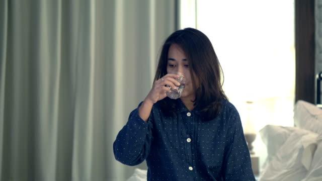 vídeos de stock, filmes e b-roll de mulheres asiáticas é água potável na cama - assoando nariz