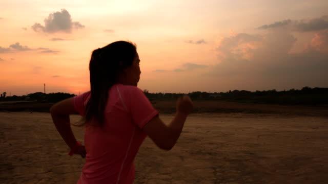 asian women jogging at sunset. - sports bra stock videos & royalty-free footage