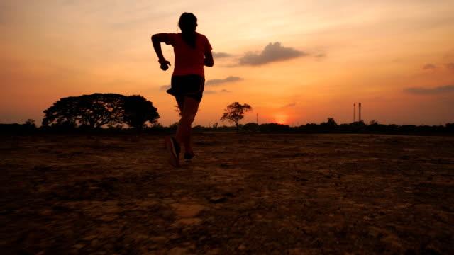 stockvideo's en b-roll-footage met aziatische vrouwen die bij zonsondergang joggen. - gymbroek
