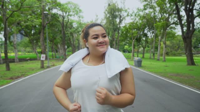 asiatische frauen joggen in der natur in der abendsonne mit den bäumen - overweight stock-videos und b-roll-filmmaterial