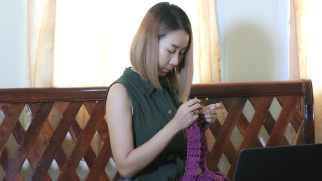 asian women learning knitting and using laptop for watching online tutorial in living room - knitting needle stock videos & royalty-free footage