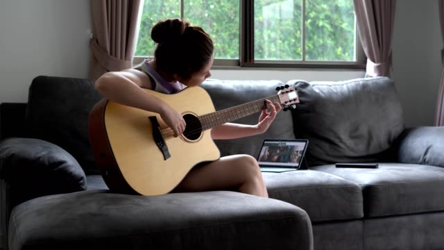 asian women learns to play the guitar with the help of an online tutorial - passion stock videos & royalty-free footage