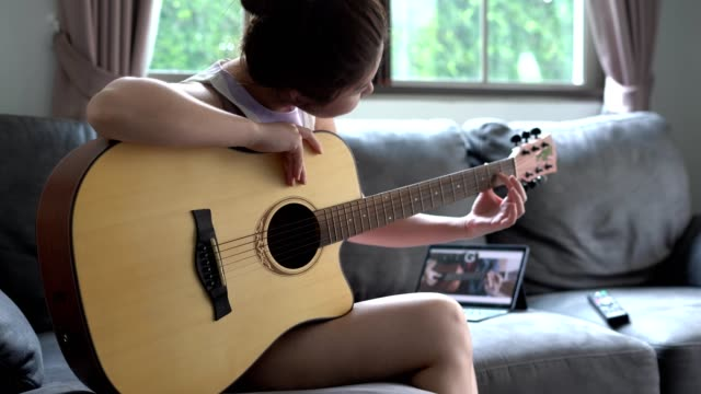 asian women learns to play the guitar with the help of an online tutorial - formazione video stock e b–roll