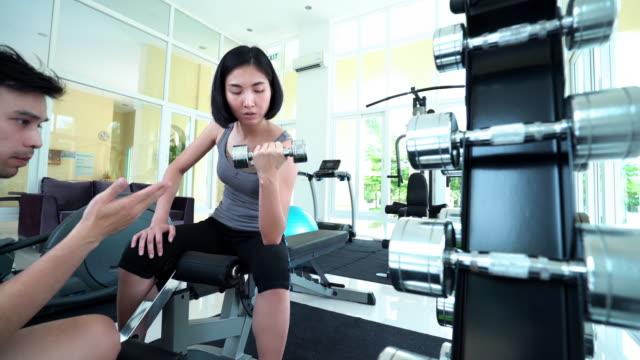 アジア女性のリフティングダンベル、パーソナルインストラクター