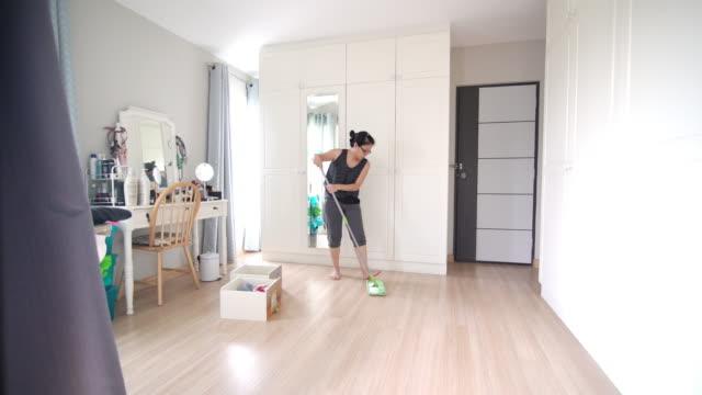 vídeos y material grabado en eventos de stock de mujeres asiáticas mopping on the floor en el vestidor de casa - barrer