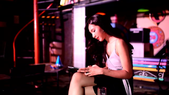 asian women play smartphone in the party