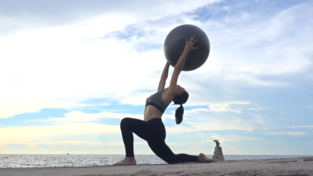 asian women practice yoga on summer seaside, yoga and healthy lifestyle concept. - fitness ball stock videos & royalty-free footage