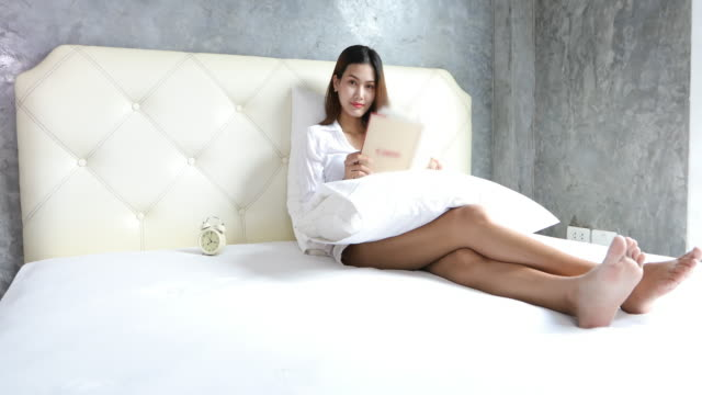 asian women reading book at white bedroom shot on amazing time to relax - bedclothes stock videos & royalty-free footage