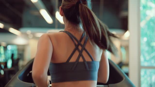 vidéos et rushes de femmes asiatiques exécutant sur le tapis roulant dans la gymnastique de sport. - entraînement cardiovasculaire