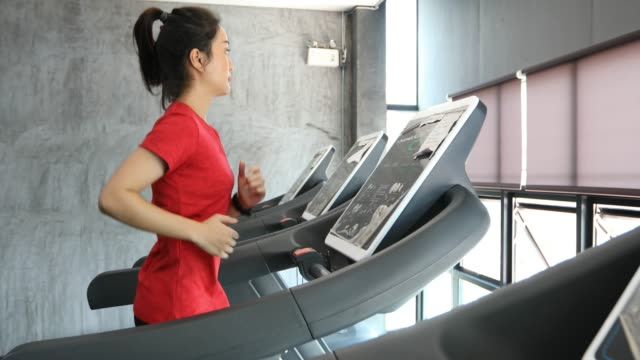 asian women running sport shoes at the gym while a young caucasian woman is having jogging on the treadmill - treadmill stock videos & royalty-free footage