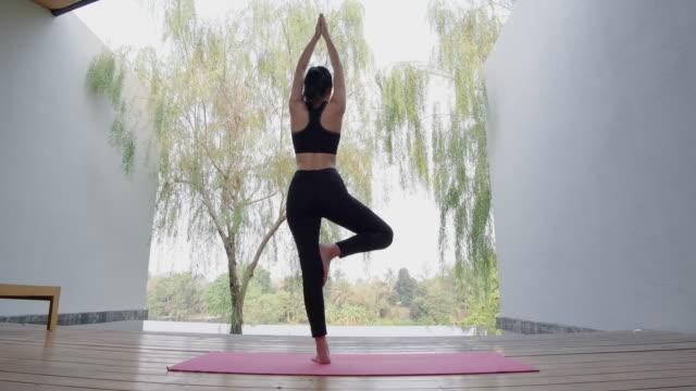 vídeos de stock, filmes e b-roll de mulheres asiáticas ela joga ioga interior na piscina. - praticando