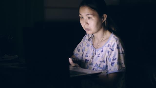 asiatische frauen sitzen im wohnzimmer mit laptop zu hause in dem schlafengehen - hot desking arbeitsplatz stock-videos und b-roll-filmmaterial