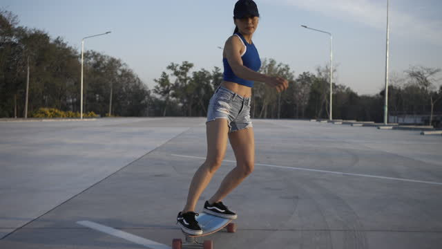 asian women surf skate or skates board outdoors on beautiful summer day. happy young women play surf skate at park on morning time. - stunt stock videos & royalty-free footage