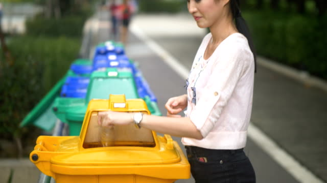 asian women throwing plastic bottle into the trash garbage - collection stock videos & royalty-free footage