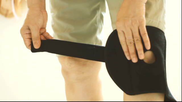 asian women to knee injury and use knee support brace on leg - leg brace stock videos and b-roll footage
