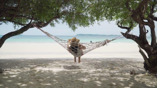 vídeos de stock, filmes e b-roll de mulheres asiáticas viajantes relaxando e jogando ukulele em um berço perto da praia. - ukulele