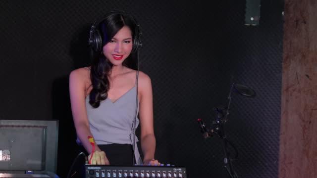 asiatische frauen dj zwicken verschiedenen track-steuerungen auf dj deck - vorderansicht stock-videos und b-roll-filmmaterial