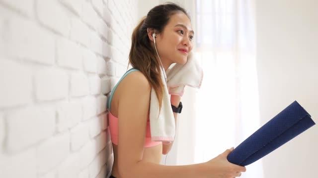 asiatische frauen verwenden ein schweißtuch und hören musik mit kopfhörer nach dem spielen yoga und bewegung zu hause hintergrund. übung für gewicht verlieren, flexibilität erhöhen und die form straffen. - handtuch stock-videos und b-roll-filmmaterial
