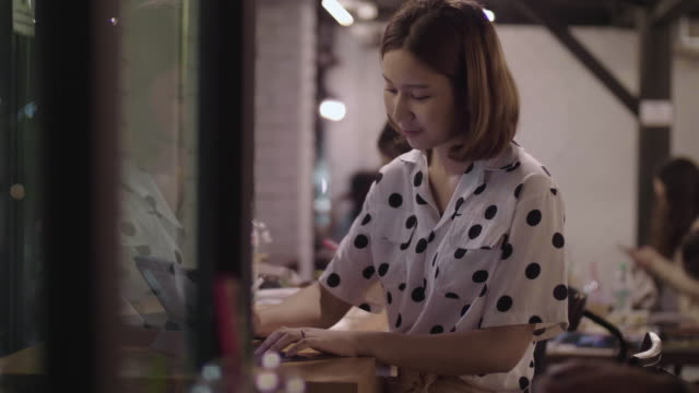 vidéos et rushes de les femmes asiatiques utilisent des ordinateurs portables pour travailler la nuit dans les cafés. - designer