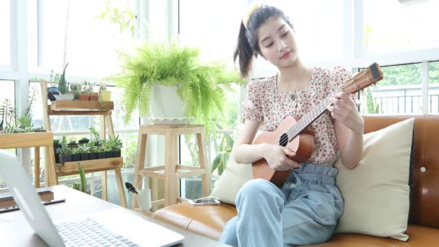 vídeos de stock, filmes e b-roll de mulheres asiáticas usam seus notebooks para estudar e praticar o ukulele na internet em casa. - ukulele